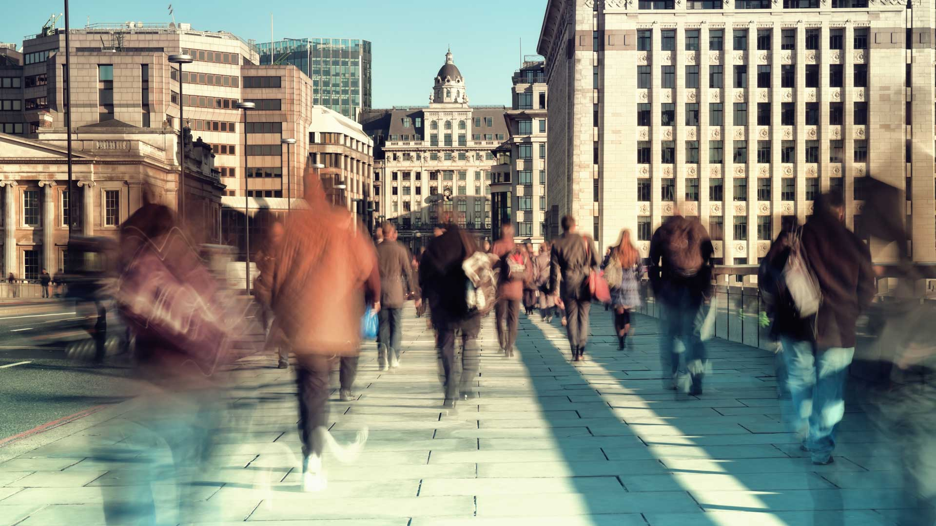 Slow shutter speed image of commuters walking over London Bridge
